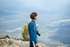 Den unga fotografen i solljus står på överkanten av ett berg arkivbild