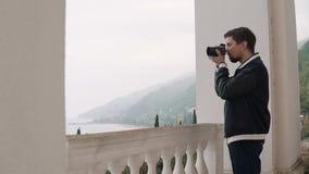 Den unga fotografen tar foto på en kamera, honom är i naturen i inre lager videofilmer
