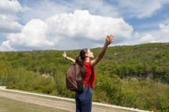 Den unga fotvandrareflickan som står över affärsföretag för begrepp för livsstil för molnlandskaplopp, semestrar utomhus- lycklig Royaltyfri Fotografi