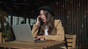 Den unga freelancerarbetarkvinnan arbetar med bärbara datorn och samtal vid telefonen i kafé lager videofilmer