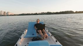 Den unga freelanceren arbetar på datoren på ett fartyg Avlägsen affär passiva förtjänster stock video