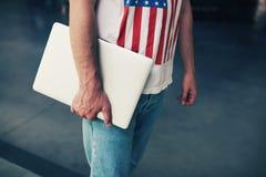 Den unga freelanceren eller affärsmannen räcker den hållande nära bärbar datordatoren royaltyfri foto