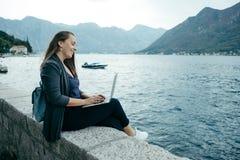 Den unga freelancerkvinnan i grå kofta och blått vandrar arbeten Arkivfoton