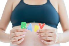 Den unga förväntansfulla modern med att stava för bokstavskvarter behandla som ett barn på den gravida buken Arkivbilder