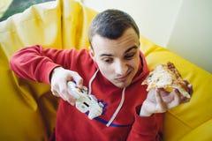Den unga gameren spelar en videospel på konsolen och ätapizza Passiv rekreation med en styrspak i deras händer Arkivbilder