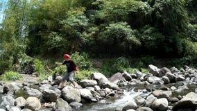 Den unga ganska damen korsar i klart stenigt vårflodvatten som är fyllt med naturlig vegetation lager videofilmer