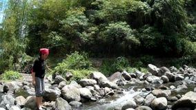 Den unga ganska damen korsar i klart stenigt vårflodvatten som är fyllt med naturlig vegetation stock video