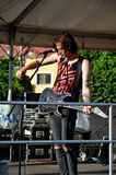 Den unga gitarristen, medlem av vaggar musikgruppen det paranoid, ställning i etapp framme av mikrofonen arkivfoto