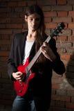 Den unga gitarristen spelar hans gitarr Arkivbild