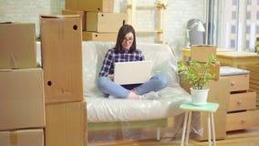 Den unga glade kvinnan använder bärbara datorn som sitter på soffan, når han har flyttat sig till en modern lägenhet lager videofilmer