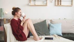 Den unga glade kvinnan gillar dricka varmt kaffe Flicka som spenderar tid på te lager videofilmer