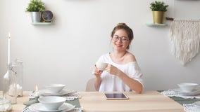 Den unga glade kvinnan gillar dricka varmt kaffe Flicka som spenderar tid på te stock video