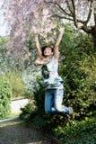 Den unga glade kvinnan hoppar under blomningträd Arkivfoto
