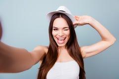 Den unga gladlynta attraktiva toothy brunhåriga damen ler på arkivfoton