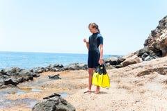 Den unga gladlynta flickan i dykningdräkt med skovlar som står på, vaggar royaltyfria bilder