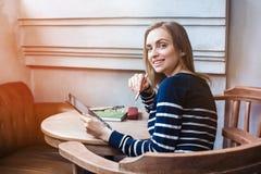 Den unga gladlynta kvinnliga studenten tycker om fri tid, medan sitter med handlagblocket i kafé inomhus Den härliga kvinnan är Royaltyfria Bilder