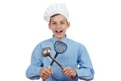Den unga gladlynta tonåringen med sleven och blidkar i en kocks hatt Isolerad studio Arkivbild