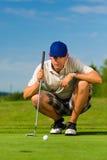 Den unga golfspelare jagar på att sätta Royaltyfri Bild