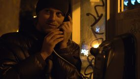 Den unga grabben är kalla och tala i telefonbås på nattstaden, kallt väder stock video