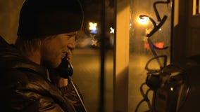 Den unga grabben är kalla och tala i telefonbås på nattstaden, kallt väder lager videofilmer