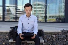 Den unga grabben i freelancerskjorta arbetar på gatan nära byggnad i staden tabell för innehav för affärsman royaltyfria bilder
