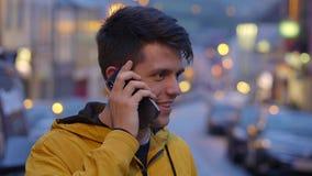 Den unga grabben kallar hans vän på hans mobiltelefon stock video