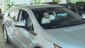 Den unga grabben kontrollerar den auto kabinen i bilåterförsäljaren lager videofilmer