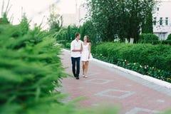 Den unga grabben kramar hans flicka, medan gå arkivfoton