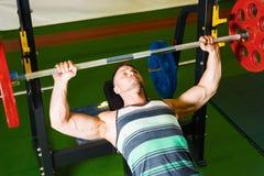 Den unga grabben lyfter skivst?ngen f?r biceps Muskul?s manutbildning i idrottshallen _ royaltyfri fotografi