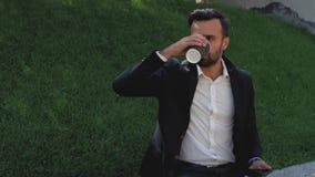Den unga grabben med ett skägg i en klassisk dräkt sitter i parkerar på en bakgrund av gräs och drinkkaffe från en disponibel kop arkivfilmer