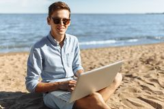 Den unga grabben med exponeringsglas som arbetar på hans bärbar dator på stranden, arbetar på semestern som är passande för annon fotografering för bildbyråer