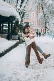 Den unga grabben och den härliga flickan har gyckel på en snöig gata Par i tröjor arkivbild