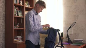 Den unga grabben samlar en ryggsäck för grupper lager videofilmer