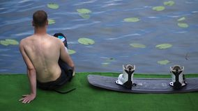 Den unga grabben sitter bredvid en wakeboard på en stege vid floden lager videofilmer