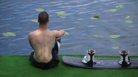 Den unga grabben sitter bredvid en wakeboard på en stege vid floden stock video