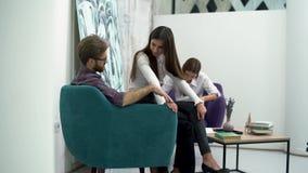 Den unga grabben som sitter i rekreationsområdet slår försiktigt, flickans hand Diskussion av arbetsplan i kopplad av stock video