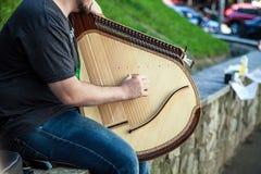 Den unga grabben spelar på ukrainsk nationell instrumentbandura Arkivfoton