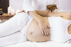 Den unga gravida kvinnan har massagebehandling på brunnsorten arkivbilder