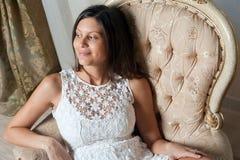 Den unga gravida kvinnan i klänning sitter på stol Royaltyfri Bild