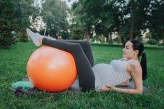 Den unga gravida kvinnan lider från smärtar i höftområde Hon som ligger på yogakompis parkerar in Modellera på hållhänder på höft arkivfoto