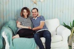 Den unga gravida kvinnan med maken på den vita soffan i blått hyr rum Iklädd randig t-skjorta för par Sommarinspiration Royaltyfri Fotografi