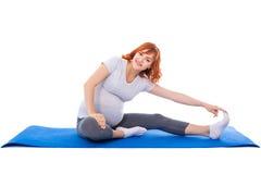 Den unga gravida kvinnan som gör sträckning, övar på matt isolator för yoga arkivbild
