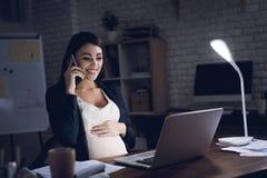 Den unga gravida kvinnan talar på telefonen på skrivbordet i mörk miljö Gravid kvinna som arbetar på bärbara datorn arkivbilder