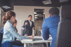 Den unga gruppen för affärsfolk har möte och arbete i modernt ljust kontor inomhus Arkivbild
