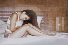 Den unga gulliga asiatiska kinesiska kvinnan på hennes 20-tal som lider period, smärtar innehavet hennes mage eller buk som känne Royaltyfria Bilder