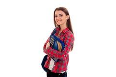 Den unga gulliga brunettstudentkvinnan med blått vandrar på hennes skuldra och mapp för anteckningsböcker i händer som ser Royaltyfria Bilder