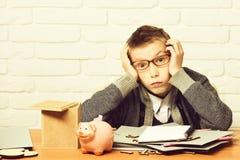 Den unga gulliga elevpojken i grå tröja och exponeringsglas som sitter på skrivbordet, lutade på händer med den rosa piggy svinba arkivfoton
