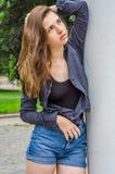 Den unga gulliga flickan med långt hår i en skjorta och en grov bomullstvill kortsluter att gå i parkera i Lviv Striysky den soli Arkivfoton