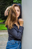 Den unga gulliga flickan med långt hår i en skjorta och en grov bomullstvill kortsluter att gå i parkera i Lviv Striysky den soli Arkivbild
