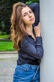Den unga gulliga flickan med långt hår i en skjorta och en grov bomullstvill kortsluter att gå i parkera i Lviv Striysky den soli Arkivbilder